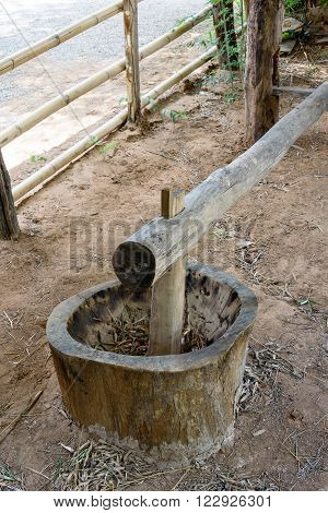 Traditional rice milling with a wooden mortar and pestle used to de-hull or separate husk to get brown rice for eating.