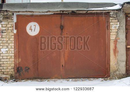 metal braun door of garage with lock. brick background