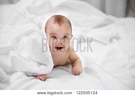 Naked adorable baby lying on soft bed, close up