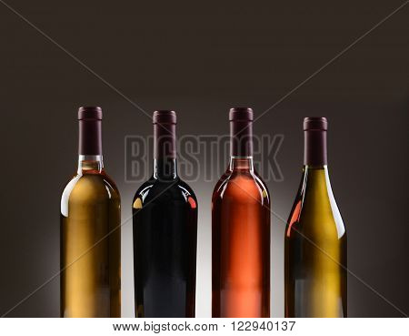 Closeup of four wine bottles with no labels on a light to dark gray background.