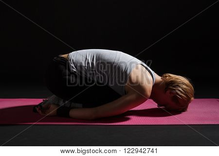 Young woman practicing yoga, Balasana / Child pose