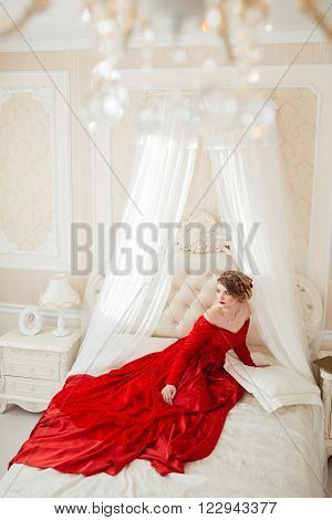Beautiful woman in a red dress lying on bed.