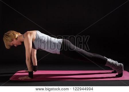 Young woman practicing yoga, Chaturanga Dandasana / Four-Limbed Staff Pose