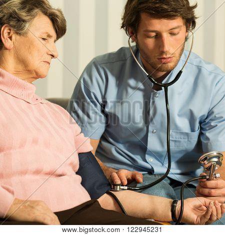 Young handsome doctor using blood pressure gauge