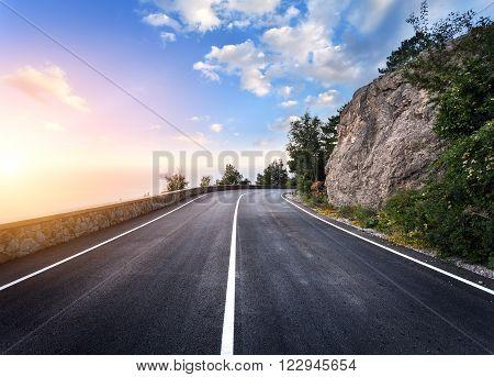 Beautiful Mountain Asphalt Road With Rocks, Blue Sky At Sunset