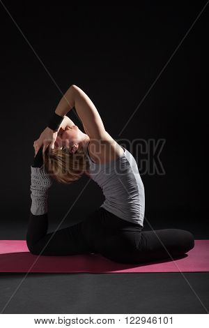 Young woman practicing yoga, Eka pada Rajakapotasana / Pigeon pose