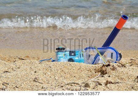 Water camera and snorkeling masque on beach sand
