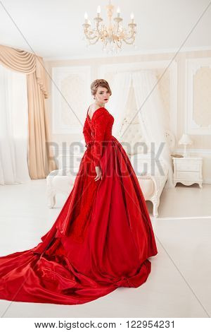 Beautiful blond woman in red posing in vintage interior