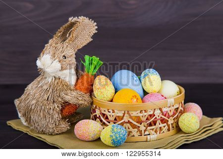 Wicker Easter Bunny With Easter Eggs In Basket On Dark Wooden Background