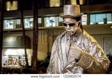 Waikiki, Honolulu, Hawaii, USA - Dec 12, 2015: Night street performer keeping very still along Kalakaua Avenue. His face is painted glittery silver to match his clothing color. Passers-by watch in awe and often donate money.