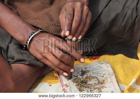 ALLAHABAD, INDIA - FEBRUARY 07, 2013: Sadhu is preparing his chillum to smoke ganja (marihuana)