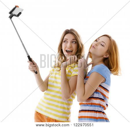 Two young women taking selfie with mobile phone isolated on white