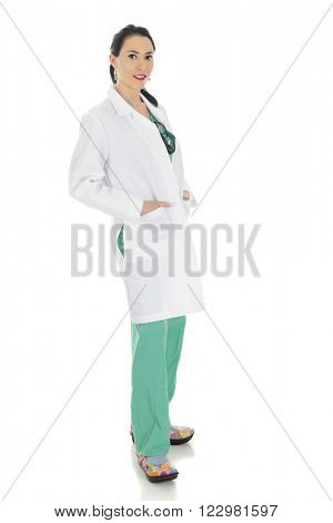 Full-length image of an attractive female doctor is scrubs and lab coat.  On a white background.