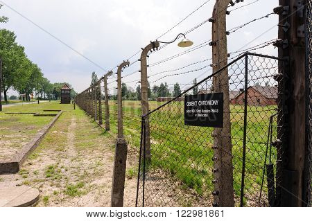 OSWIECIM, POLAND - JULY 3, 2009: Auschwitz II - Birkenau Sector I outer perimeter electrified fence and watch tower