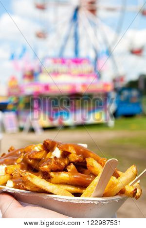 fries with poutine cheese curds and gravy in the foreground held against a background of fair booth and ferris wheel