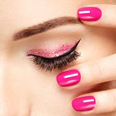 Closeup woman face with pink nails near eyes. Fingernails with pink manicure poster