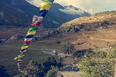 Panoramic view of a mountain valley with praying flags. Braga village in Annapurna circuit in Nepal. poster