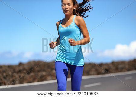 Cardio running sport woman runner jogging outside doing weight loss workout. Asian girl running fast in sun wearing blue activewear.