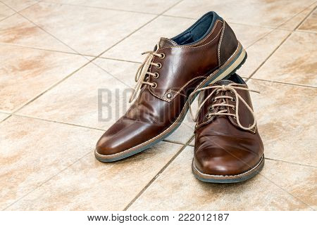 Pair of fashion brown men's shoes with shoestring on a light brown ceramic tiles
