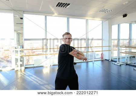 Ballroom dancer warm up before training, fair-haired tattooed guy wearing comfortable black sport clothes. Male wag legs in gym with big windows and mirrors. Concept of choreographic school, hall for group or individual workouts, sportswear.