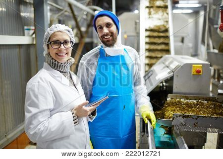 Succesful workers of seafood producing factory in uniform looking at camera at work