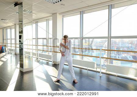 Male dancer in making sweeps on floor of studio with large windows. Boy wears black sport suit. Concept of break dance spinning.