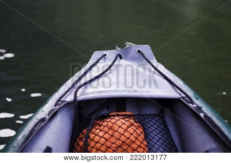 Close up of a front of inflatable canoe boat with river or lake in the background