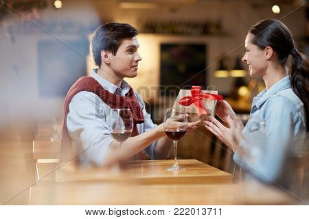 Amorous guy giving his girlfriend box with present for valentine day