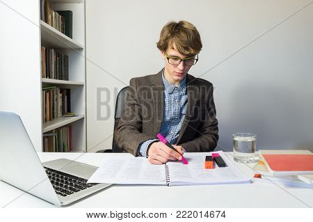Young male student works with books and laptop on home assignment or project. Handsome young person in reading eyeglasses at modern minimalistic workplace