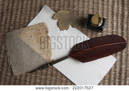 Still life with antique feather quill, inkwell and aged blank paper and dried leaf from above