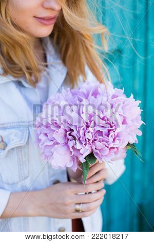 Young female hands holding beautiful tender bouquet of artificial pink peonies on mint green background. Spring bunch.
