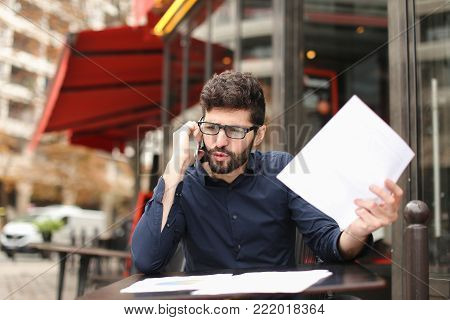 Businessman arguing, discussing project with partner by smartphone and reading papers at cafe table. Handsome man has fleecy dark hair Concept of tariff plan for long conversations and making biz decisions.