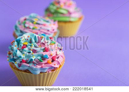 Two Cupcakes With Creamy Multicolored Top With Colorful Hearts And Sprinkles On Violet Background
