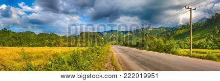 Road, rice field and mountains. Beautiful rural landscape. Vang Vieng, Laos. Panorama