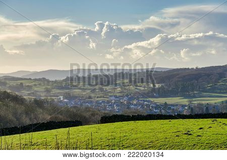 A green field with a village beyond and gowing cumulous clouds ont eh horizon, Cumbria, northern England