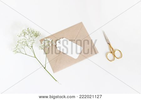 White gift tag with craft paper envelope, golden scissors and baby's breath Gypsophila flowers isolated on white table background, wedding or birthday styled stock photo, top view, flat lay composition.