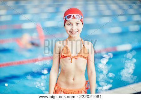 Cute little girl in swimsuit, swim-cap and goggles standing by swimming-pool