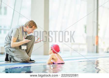 Swim trainer explaining one of his learners rules of good swimming
