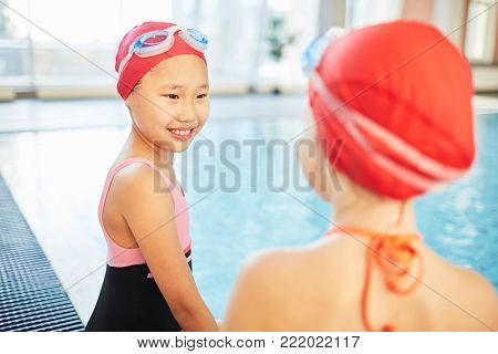 Cute Asian girl in swim-cap and goggles talking to her friend in swimming-pool