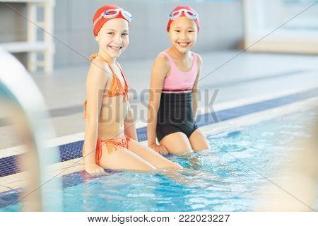 Young schoolgirls in swimwear, swim-caps and goggles sitting by swimming-pool with their legs in water poster