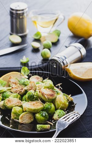 Homemade Roasted Brussel Sprouts with Parmesan cheese, lemon, Salt, Pepper on a black wooden table.