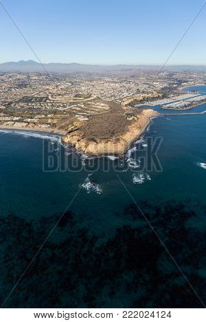 Aerial view of kelp filled pacific ocean water and Dana Point in Orange County, California.