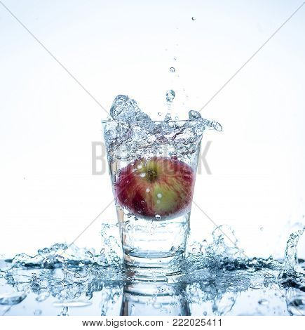 Red Apple Has Droping To The Glass And Splashing Water Around The Glass And On The Table With Reflec