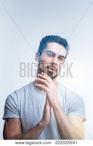 Time for changes. Creative positive pensive man chafing  hands and  thinking while posing on the isolated background