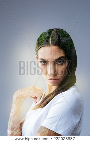 Nature gives idea. Thoughtful prominent brunette woman  gazing at the camera  and  demonstrating power while touching shoulder
