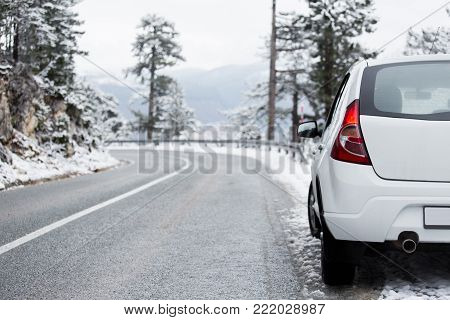 White car on a winter road through a snow covered forest. Side view