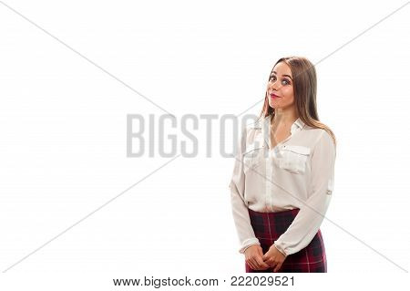 Positive young beautiful girl in formal attire smiles and stands on white background. Copyspace