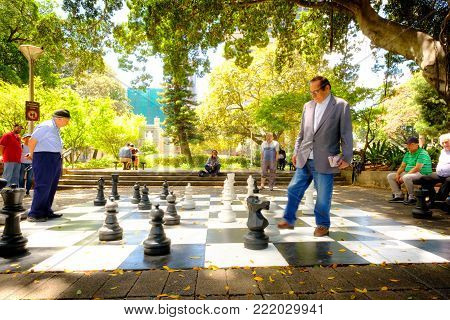 Happy Time. The Old Men  Are Playing The Giant Chess Together On The Pavement Beside The Street In H
