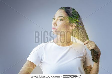 Time to rest.  Pretty earnest musing woman posing on the grey background and holding her hair while preparing for actions