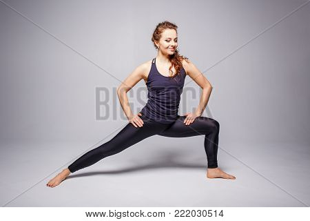 Young slim woman practising yoga against grey background. Cheerful girl stretching her legs